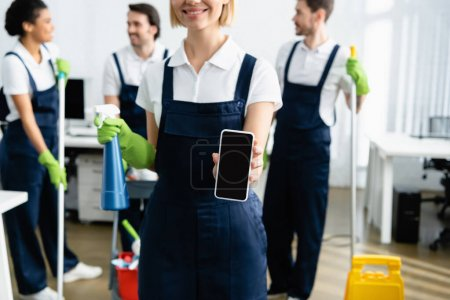 Smiling worker of cleaning company holding smartphone and detergent on blurred background in office