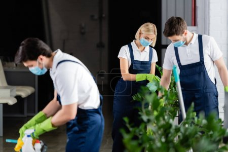 Workers of cleaning company in medical masks working in office
