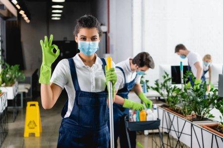 Photo pour Travailleur afro-américain de l'entreprise de nettoyage dans un masque médical tenant la serpillière et montrant un geste correct au bureau - image libre de droit