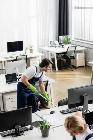 Smiling cleaner washing floor near computers in office