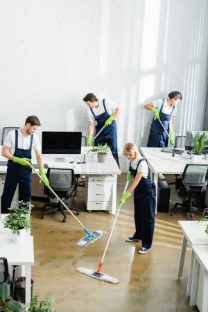 Multiethnic cleaners washing floor in modern office