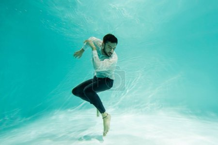Photo for Arabian businessman swimming underwater in pool - Royalty Free Image