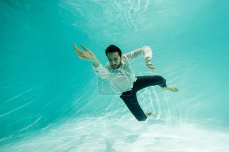 Photo pour Jeune homme d'affaires musulman les yeux fermés nageant sous l'eau dans la piscine - image libre de droit