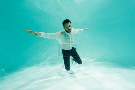 Photo for Muslim businessman in shirt diving in swimming pool - Royalty Free Image
