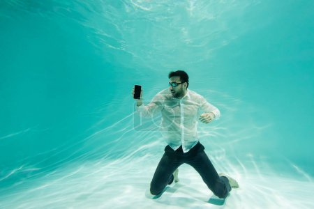 Photo for Arabian businessman in formal wear and goggles holding smartphone with blank screen underwater - Royalty Free Image