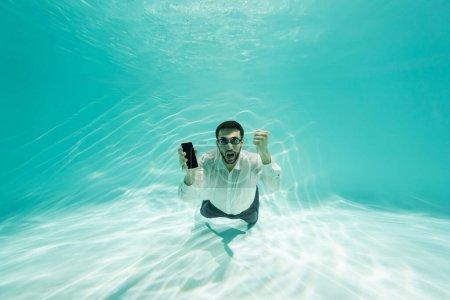 Photo pour Homme d'affaires musulman en lunettes tenant un smartphone et montrant un geste oui sous l'eau - image libre de droit