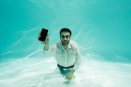 Photo for Positive arabian businessman showing smartphone with blank screen in swimming pool - Royalty Free Image