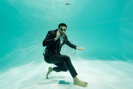 Photo for Arabian businessman looking at camera while talking on smartphone underwater in pool - Royalty Free Image