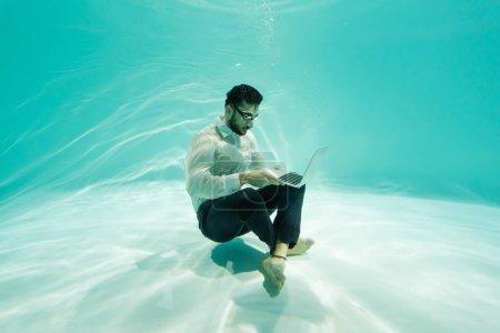 Photo pour Arabe homme d'affaires utilisant ordinateur portable sous l'eau dans la piscine - image libre de droit