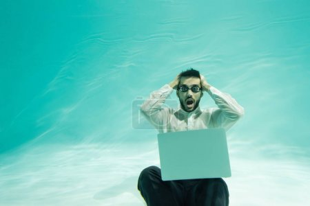 Photo for Amazed arabian businessman in goggles looking at camera near laptop in swimming pool - Royalty Free Image
