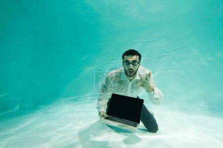 Photo pour Homme d'affaires arabe excité tenant ordinateur portable avec écran vide sous l'eau - image libre de droit