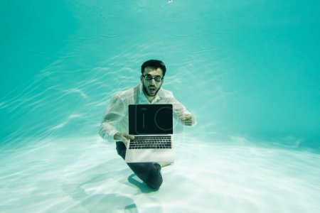 Photo for Amazed arabian businessman pointing at laptop with blank screen underwater in swimming pool - Royalty Free Image