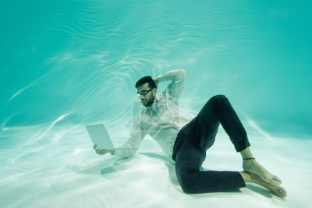 Photo for Arabian businessman looking at laptop while swimming underwater - Royalty Free Image