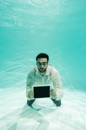 Photo pour Arabe gestionnaire dans les lunettes tenant tablette numérique sous l'eau - image libre de droit