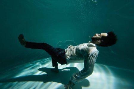 Photo pour Homme d'affaires arabe flottant près du fond de la piscine avec de la lumière - image libre de droit