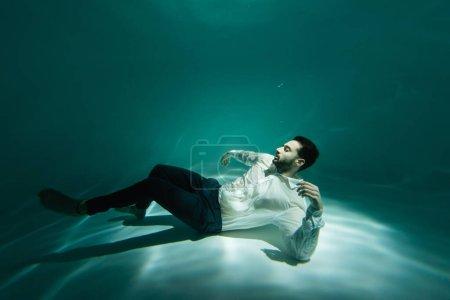 Photo pour Homme d'affaires musulman nageant sous l'eau dans la piscine - image libre de droit