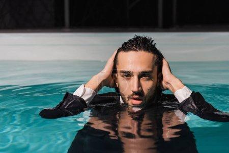Foto de Empresario musulmán barbudo mirando la cámara en la piscina - Imagen libre de derechos