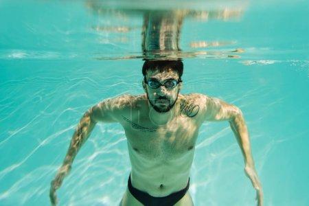 Photo pour Nageur arabe tatoué dans des lunettes regardant la caméra sous-marine - image libre de droit