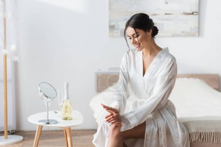 smiling bride in satin robe sitting near mirror and champagne on bedside table