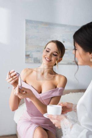 elegante Brautjungfer hält Halskette in der Nähe Braut hält Kaffeetasse im Schlafzimmer