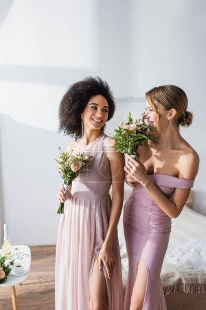 emocionado interracial damas de honor sonriendo el uno al otro mientras la celebración de ramos de boda