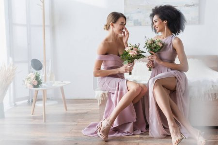cheerful interracial bridesmaids holding wedding bouquets while talking in bedroom