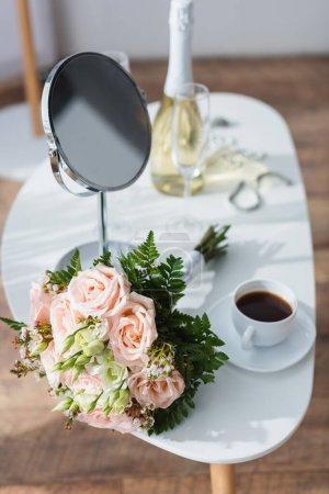 wedding bouquet, mirror and coffee cup near champagne bottle on blurred background