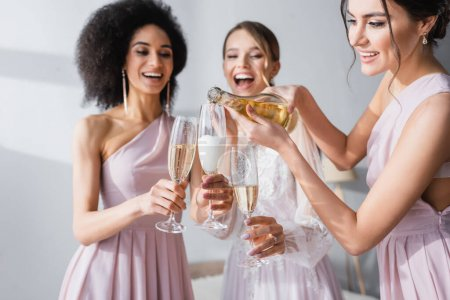 young woman pouring champagne near african american friend and bride on blurred background