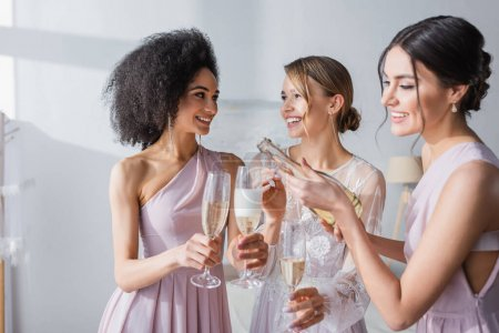 smiling woman pouring champagne near happy bride and african american bridesmaid
