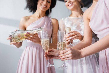 Photo for Cropped view of african american woman pouring champagne into glasses of bride and bridesmaid, blurred background - Royalty Free Image