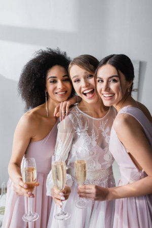 excited bride with friends smiling at camera while holding champagne glasses