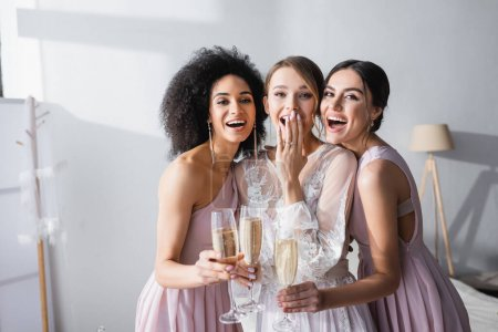 Photo pour Mariée riante couvrant la bouche avec la main près de demoiselles d'honneur interracial avec des verres de champagne - image libre de droit