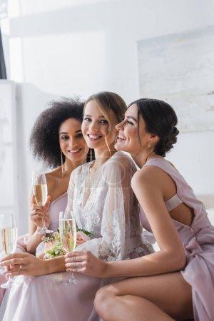 novia feliz mirando a la cámara cerca de damas de honor multiculturales con copas de champán en el dormitorio