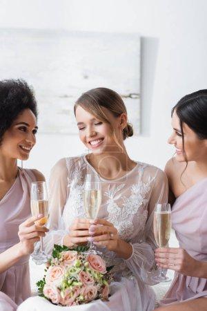 damas de honor multiculturales mirando a la novia feliz mientras sostiene copas de champán