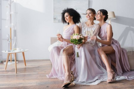 Photo for Elegant interracial bridesmaids holding champagne glasses while sitting near bride in bedroom - Royalty Free Image