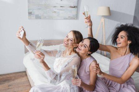 Foto de Novia emocionada tomando selfie con amigos interracial en el dormitorio - Imagen libre de derechos