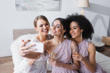 Photo pour Femme gaie prenant selfie avec mariée et ami afro-américain dans la chambre - image libre de droit