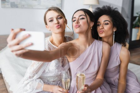 pretty bride with multicultural bridesmaids blowing air kisses while taking selfie on blurred foreground