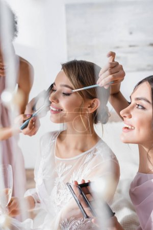 Photo for Multicultural bridesmaids doing visage to happy bride on blurred foreground - Royalty Free Image