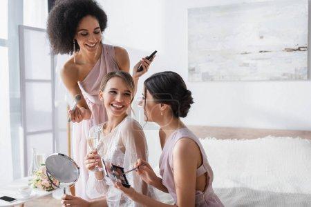 Photo pour Joyeuse mariée tenant miroir et verre de champagne près de demoiselles d'honneur multiculturelles avec des cosmétiques décoratifs - image libre de droit