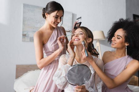 Photo for Interracial bridesmaids doing makeup to happy bride holding mirror in bedroom - Royalty Free Image