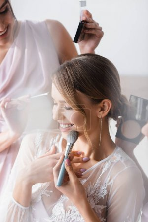 Photo for Joyful bride touching chest while bridesmaids applying makeup, blurred foreground - Royalty Free Image