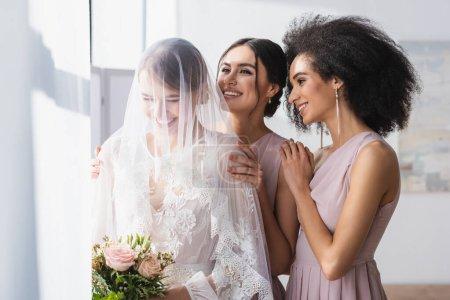 Photo pour Mariée heureuse tenant bouquet de mariage près de souriantes demoiselles d'honneur interracial - image libre de droit