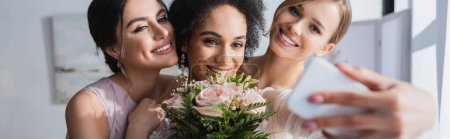 Photo for Happy african american woman taking selfie with wedding bouquet and friends, blurred foreground, banner - Royalty Free Image