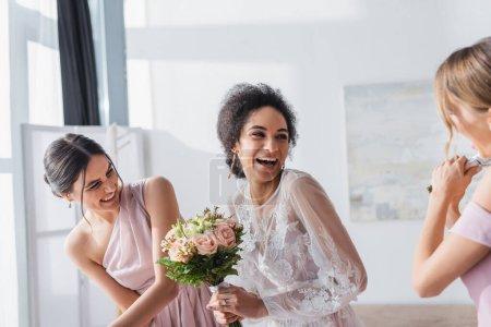 Photo pour Excitée mariée afro-américaine tenant bouquet de mariage et riant près de demoiselles d'honneur - image libre de droit