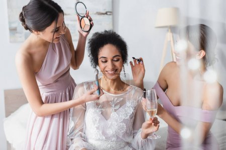 Photo for Cheerful african american bride holding champagne glass while friends applying makeup, blurred foreground - Royalty Free Image