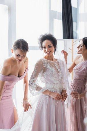 Photo pour Jeunes demoiselles d'honneur préparant jolie femme afro-américaine pour le mariage à la maison - image libre de droit