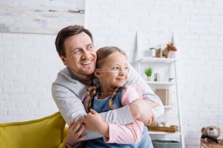 joyful girl with dad looking away while embracing at home