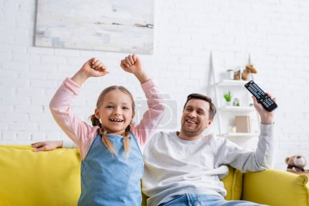 cheerful girl showing triumph gesture while watching tv near dad at home
