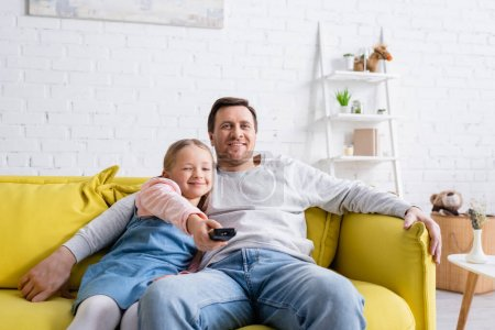 happy man watching tv with daughter clicking channels on remote controller